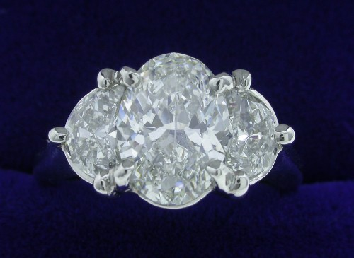 Oval Cut Diamond Ring: 1.50 carat with 0.61 tcw half moon side stones