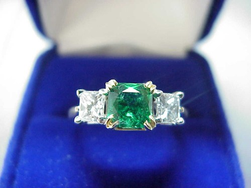 Radiant Cut Diamond Ring: 0.80 carat green Emerald with 0.71 tcw Princess side stones_
